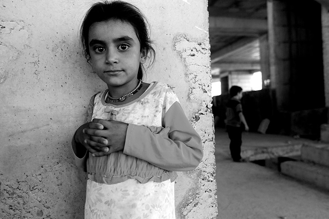 An Iraqi Yazidi girl, who fled her home when Islamic State (IS) militants attacked the town of Sinjar, poses for a photo inside a building under construction where she found refuge on the outskirts of the Kurdish city of Dohuk, in Iraq's autonomous Kurdistan region, on August 16, 2014. According to the human rights non-governmental organisation Amnesty International some 200,000 people have escaped to safety in Iraq's Kurdish region. AFP PHOTO/AHMAD AL-RUBAYE (Photo credit should read AHMAD AL-RUBAYE/AFP/Getty Images)