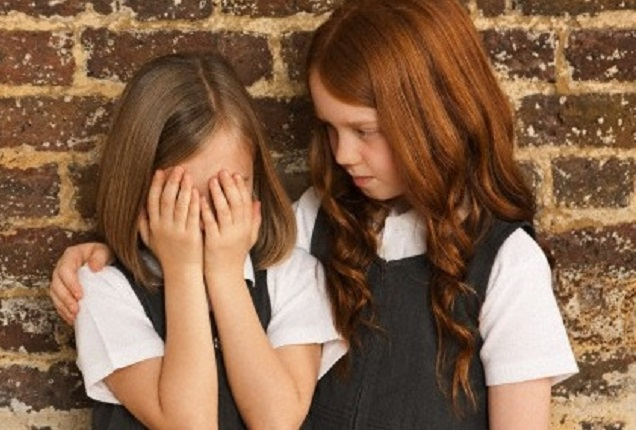 Girl comforting her friend --- Image by © Dan Pangbourne/Image Source/Corbis